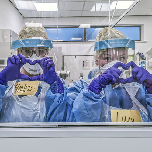 Nurses in PPE holding up love hearts
